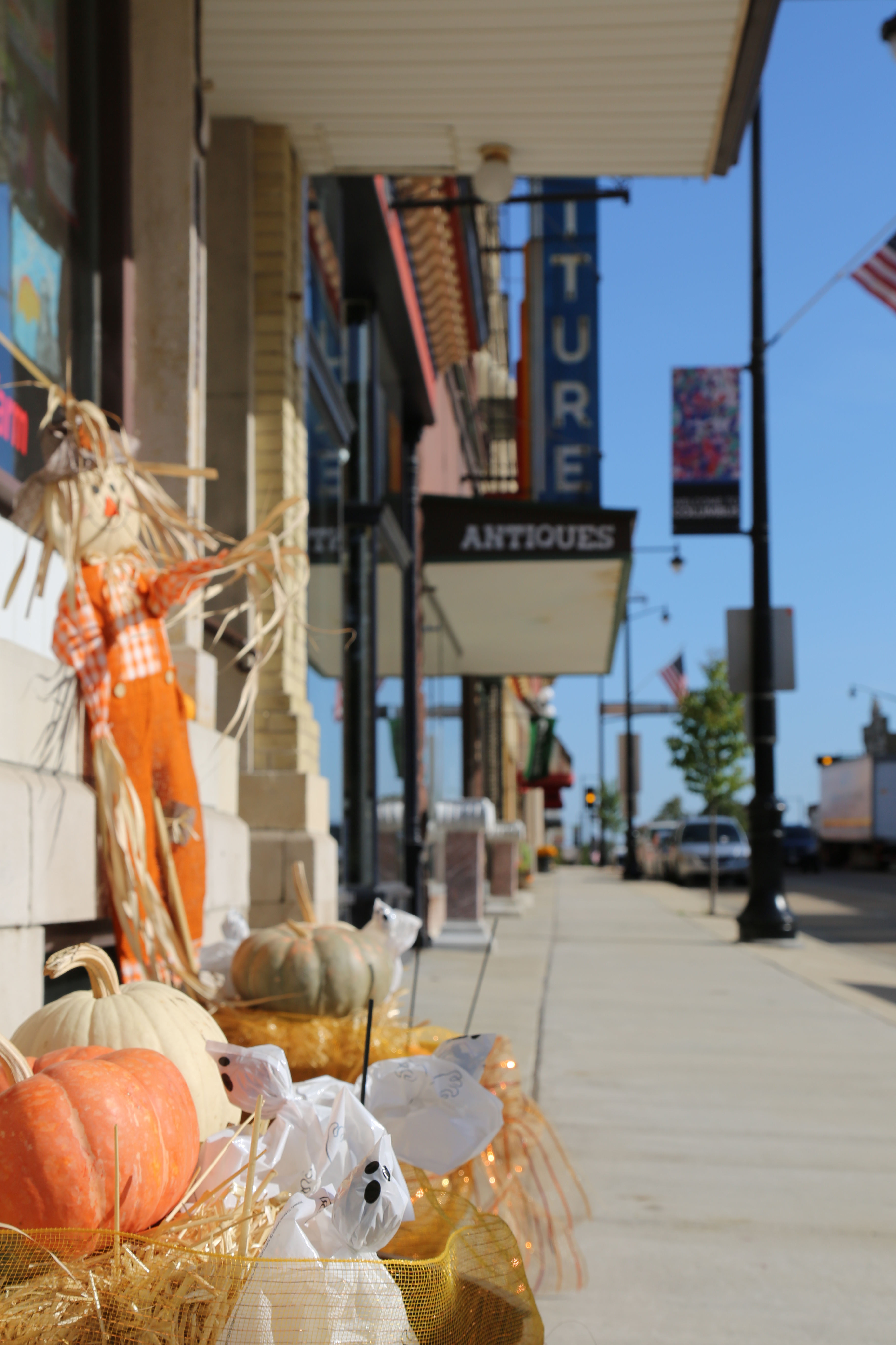 Scarecrows, straw bales, and pumpkins in front of a down town shop